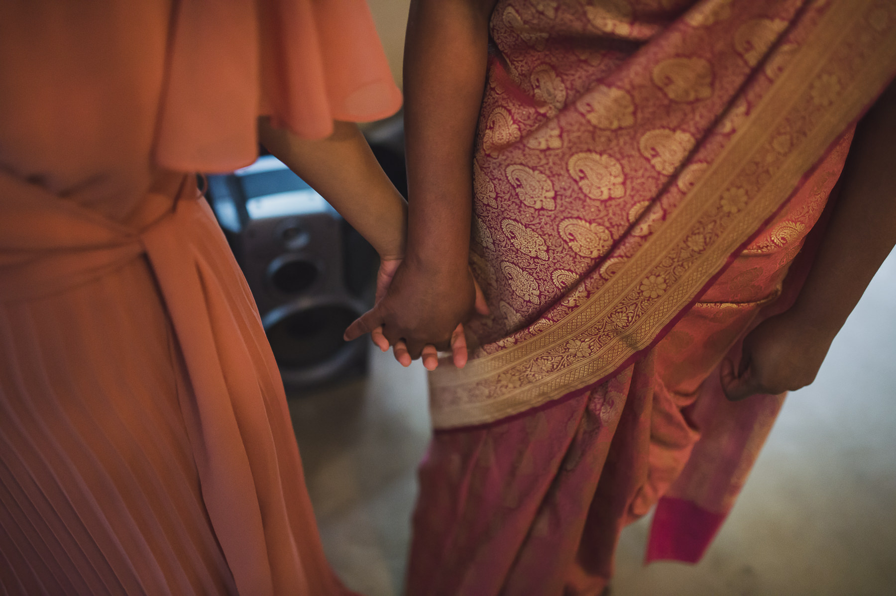 Mum holding hand of bridesmaid for comfort