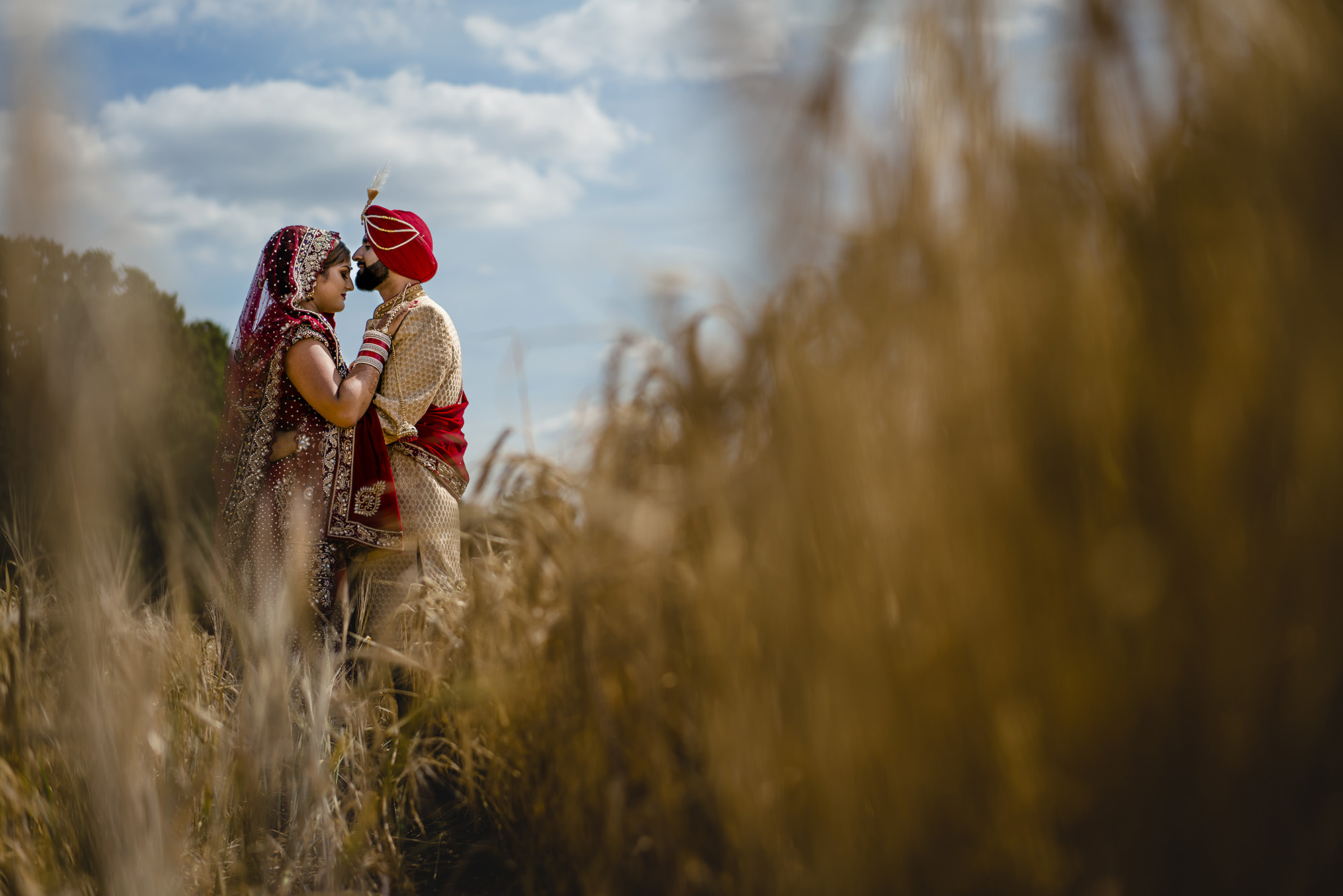 bride and groom in the field at quendon hall in their indian wedding outfits