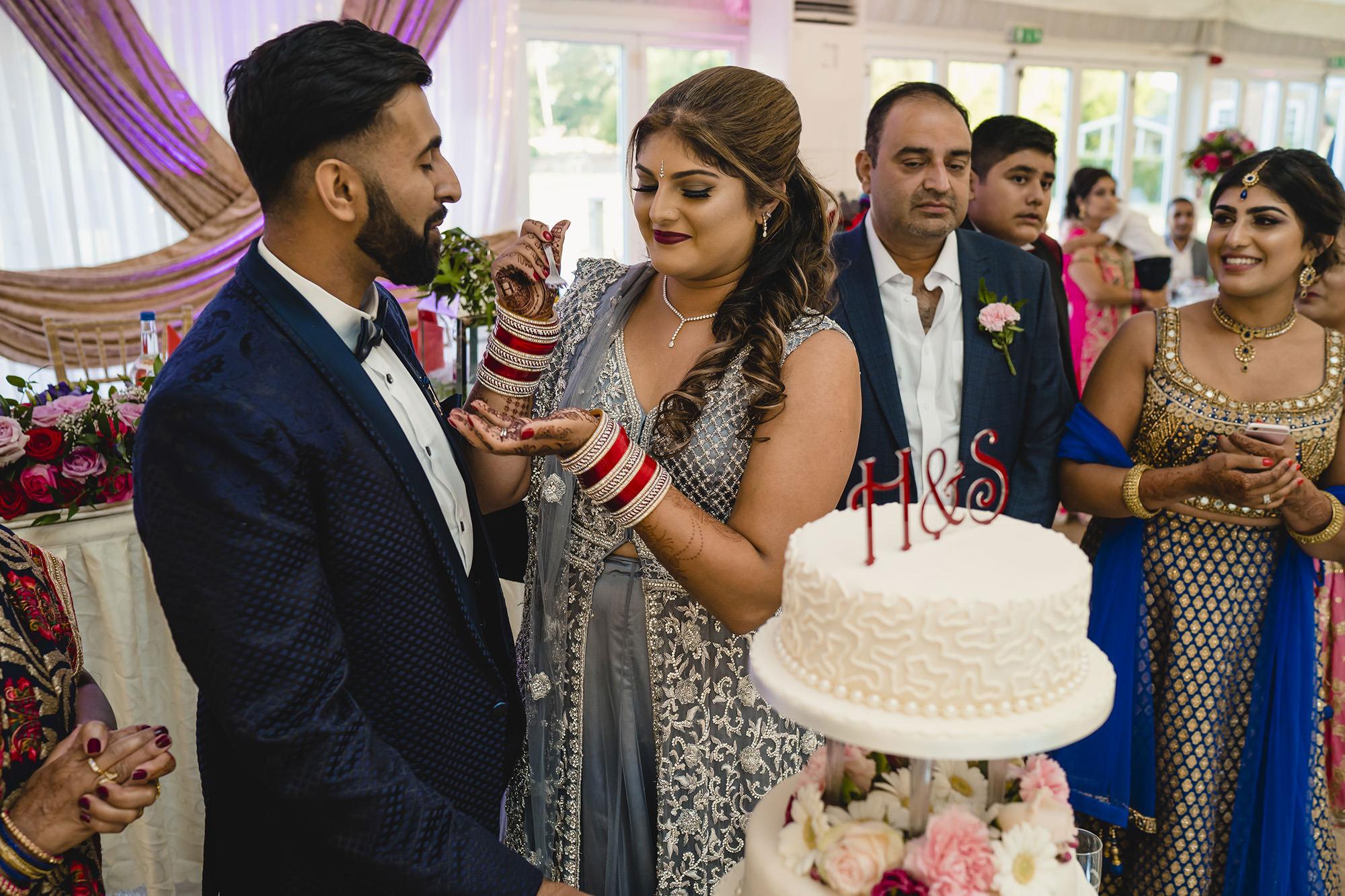 birde and groom cutting wedding cake at their wedding reception