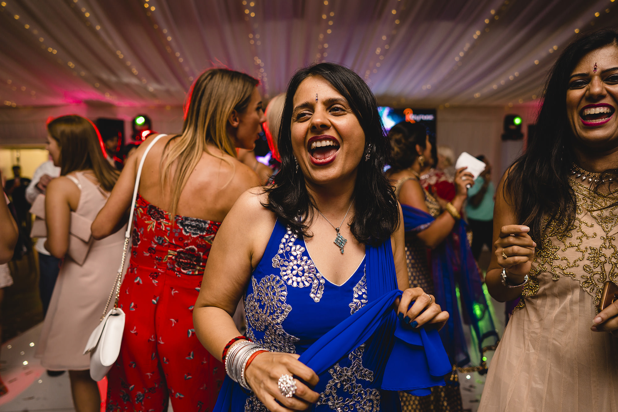 friends dancing at the asian wedding reception
