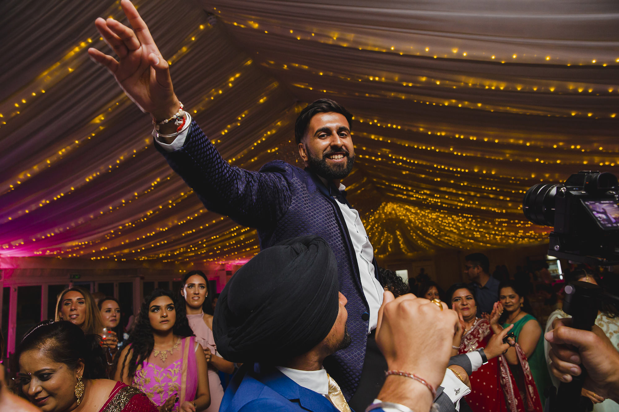groom on friends shoulders at his reception party