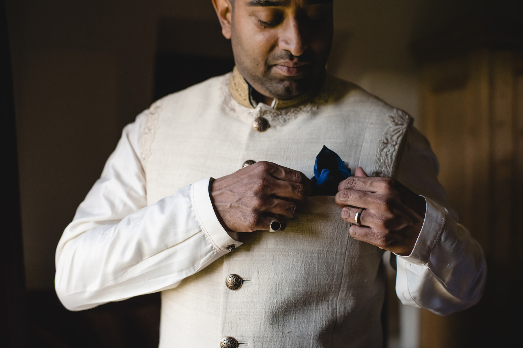 groom getting ready into his indian wedding outfit