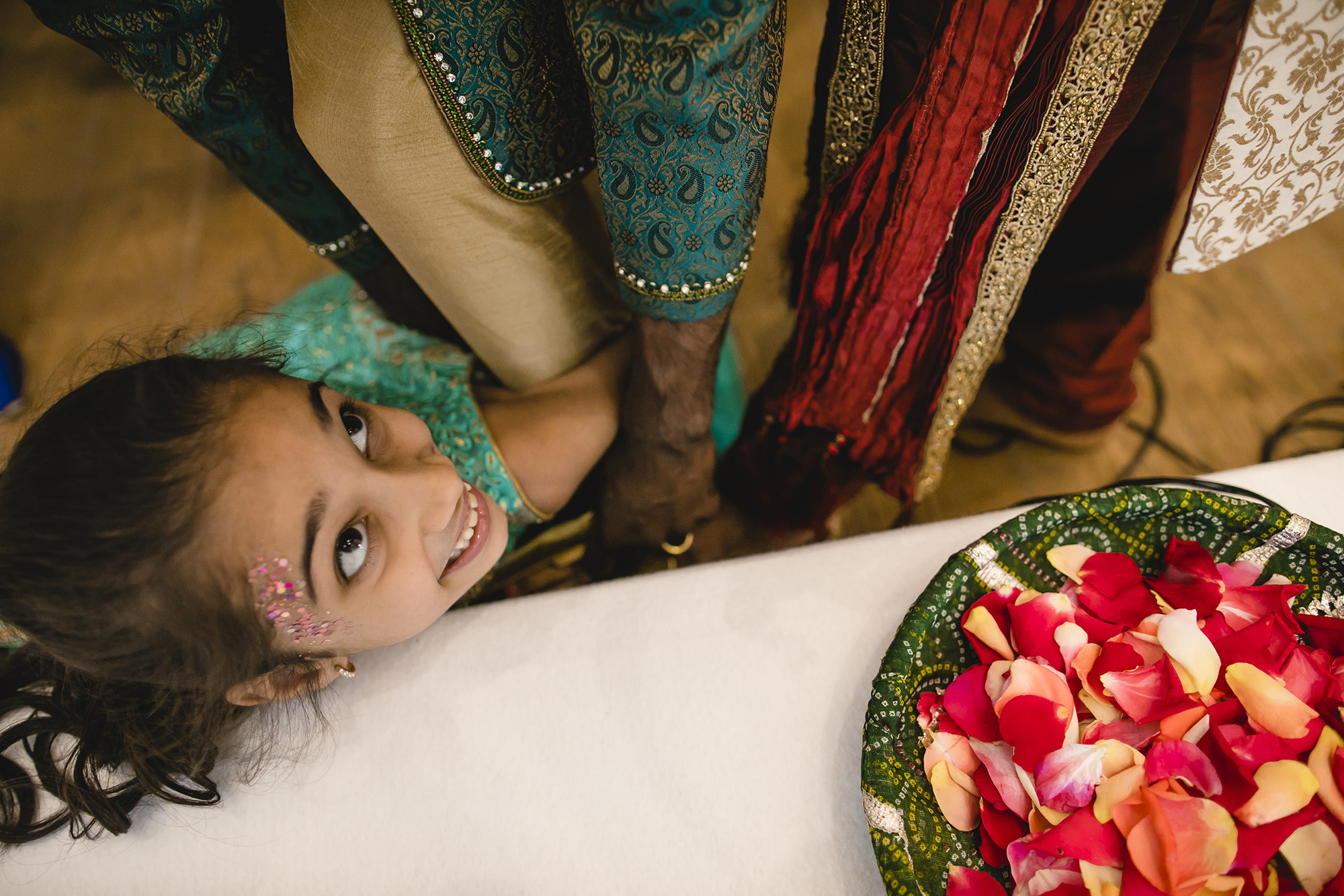 young girl stealing the grooms shoes at the indian wedding at Oswhal House