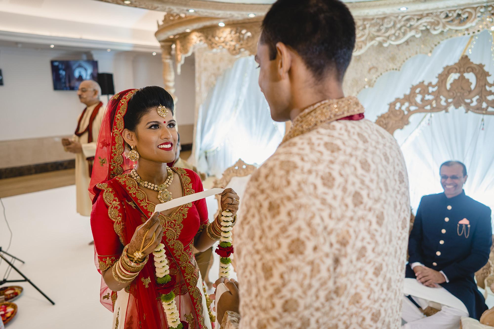 bride placing garland on groom in the hindu wedding