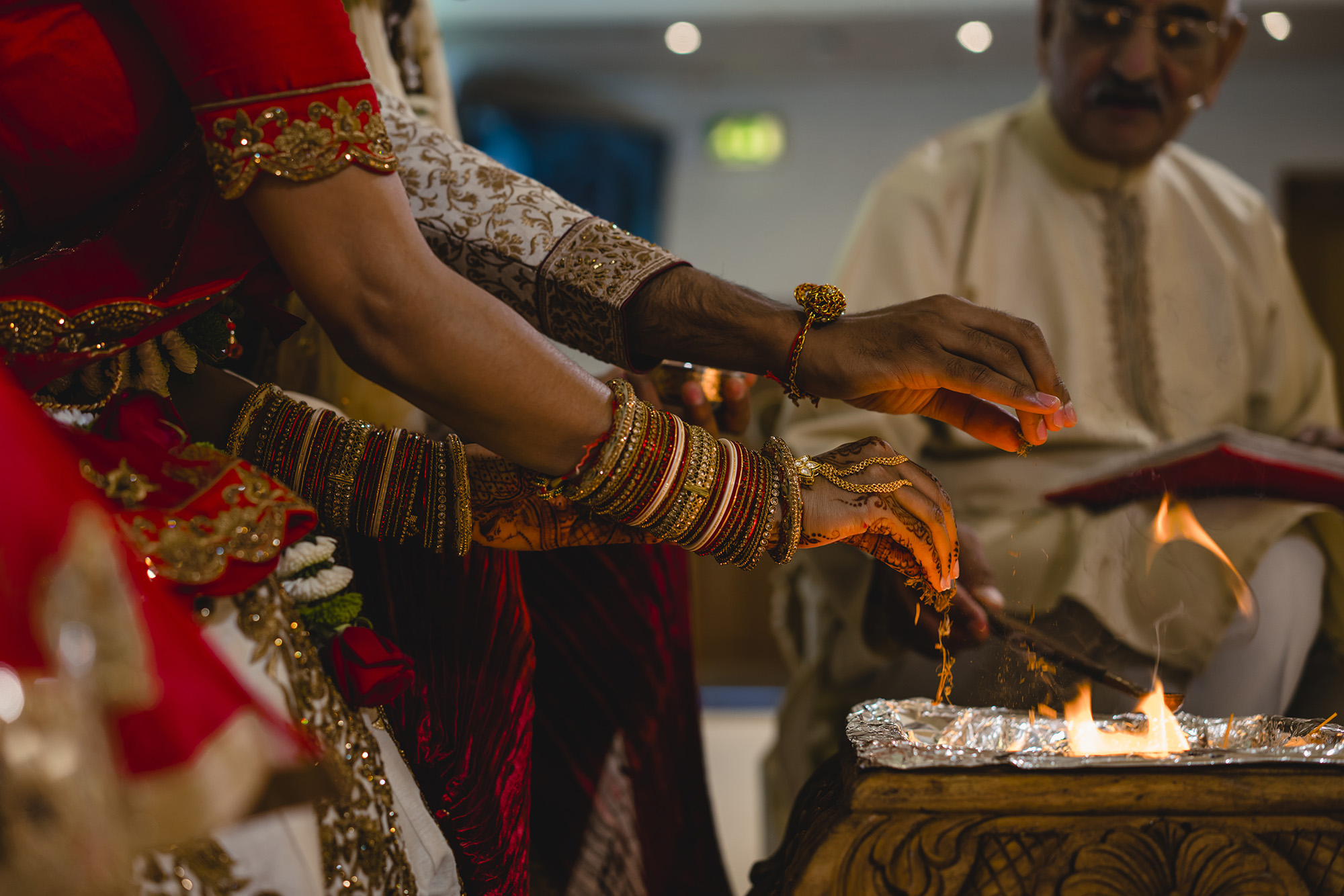 bride and groom feeding the fire at oshwal house wedding