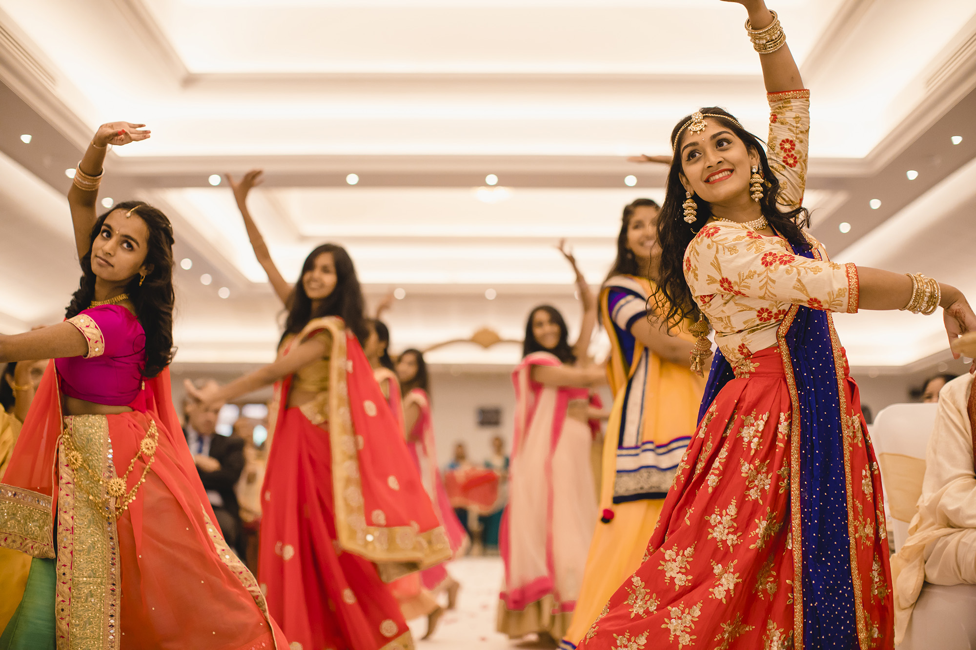 bridesmaids dancing in the aisle as the brides chunni is brought into the ceremony