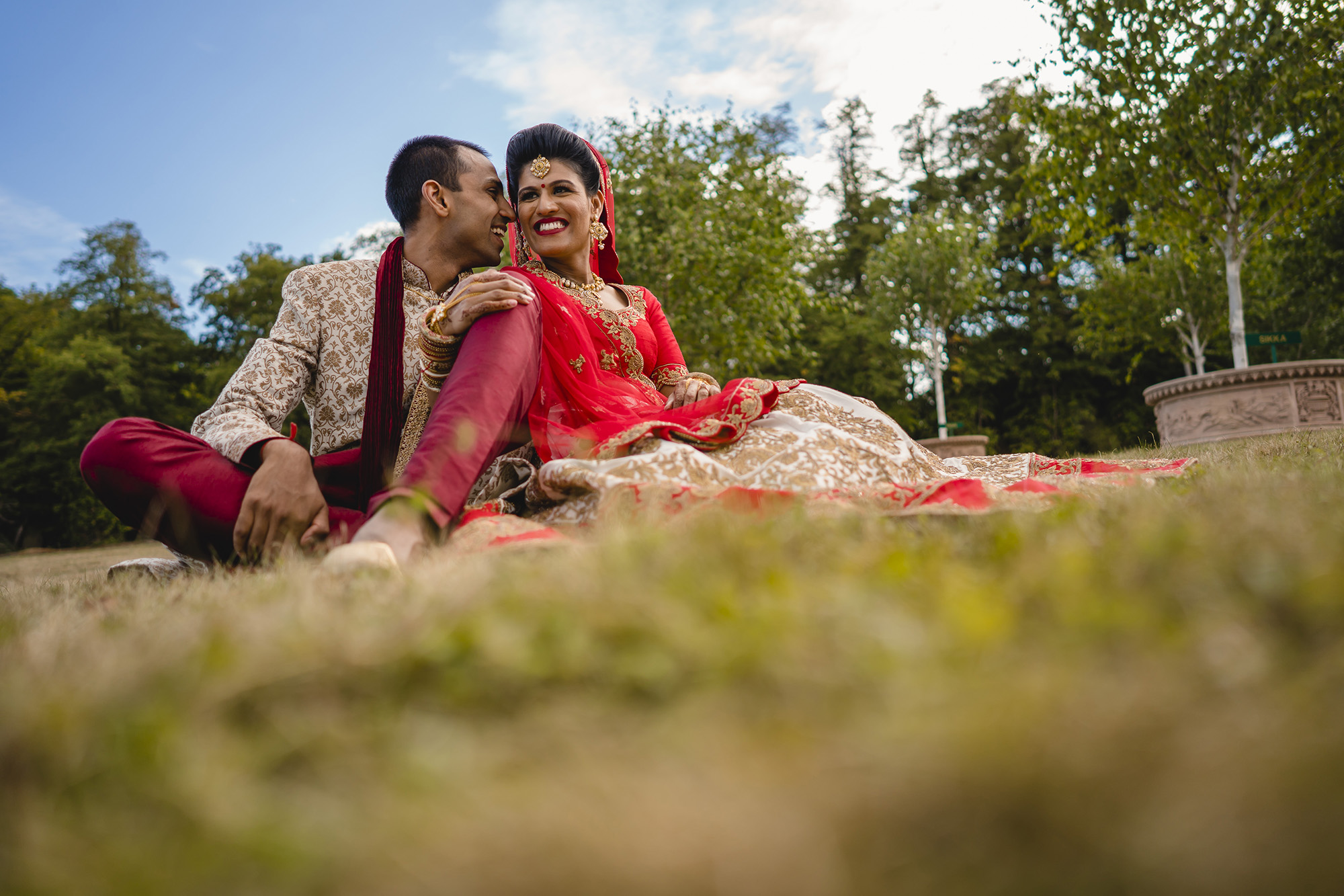 bride and groom portrait while sat on the grass
