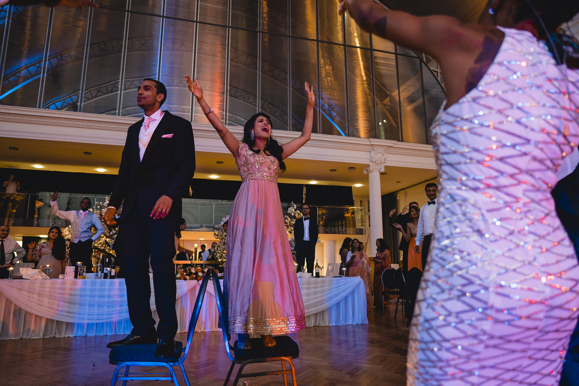 bride and groom dancing on chairs at their reception at RHH
