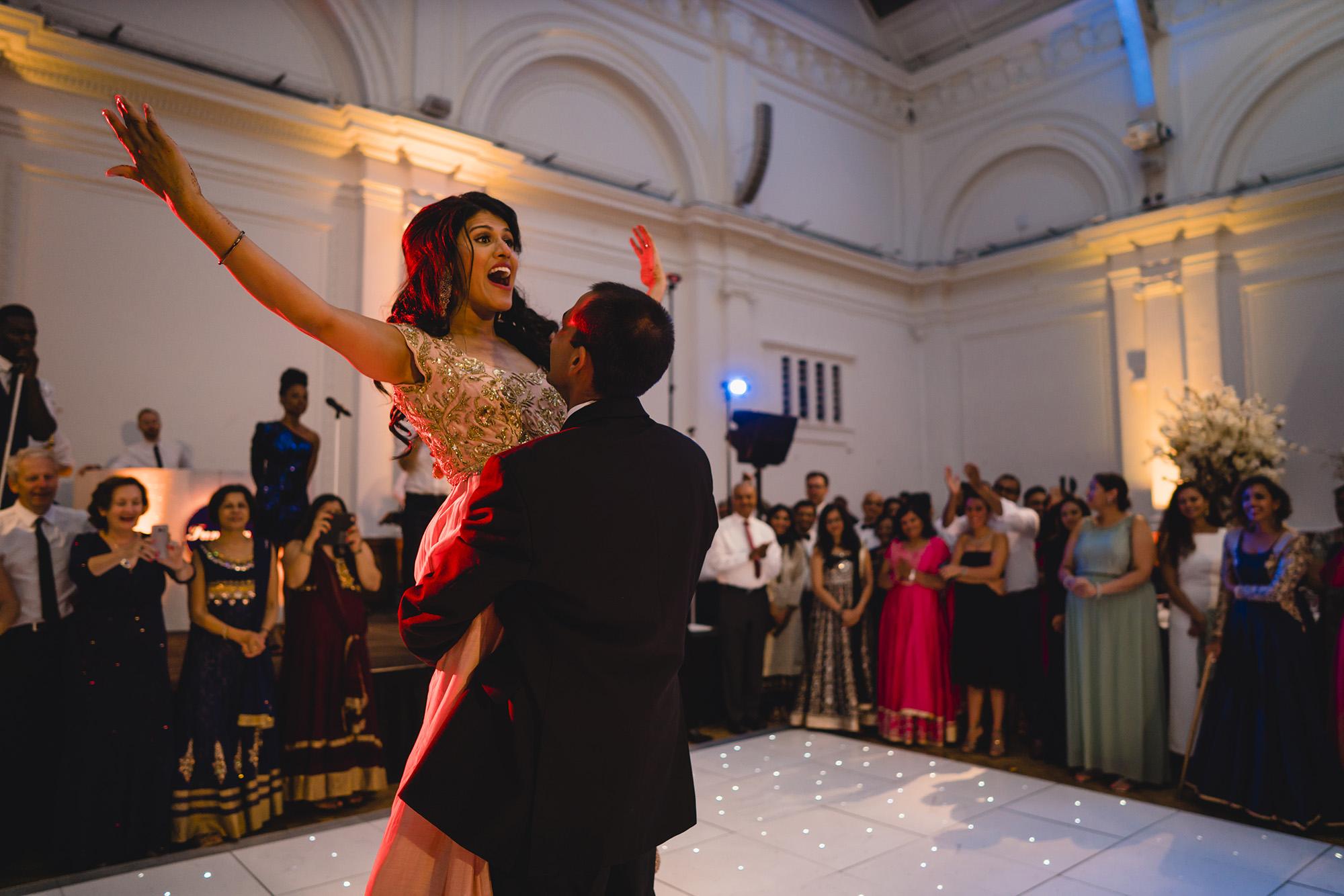 bride lifted by groom on dancefloor