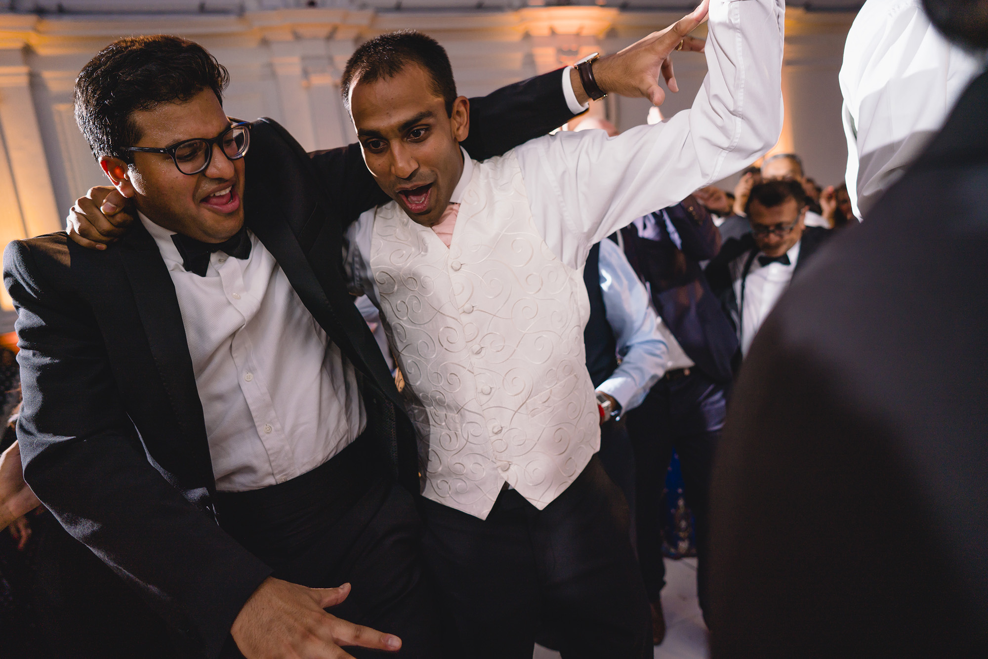 groom and friends dancing at wedding reception