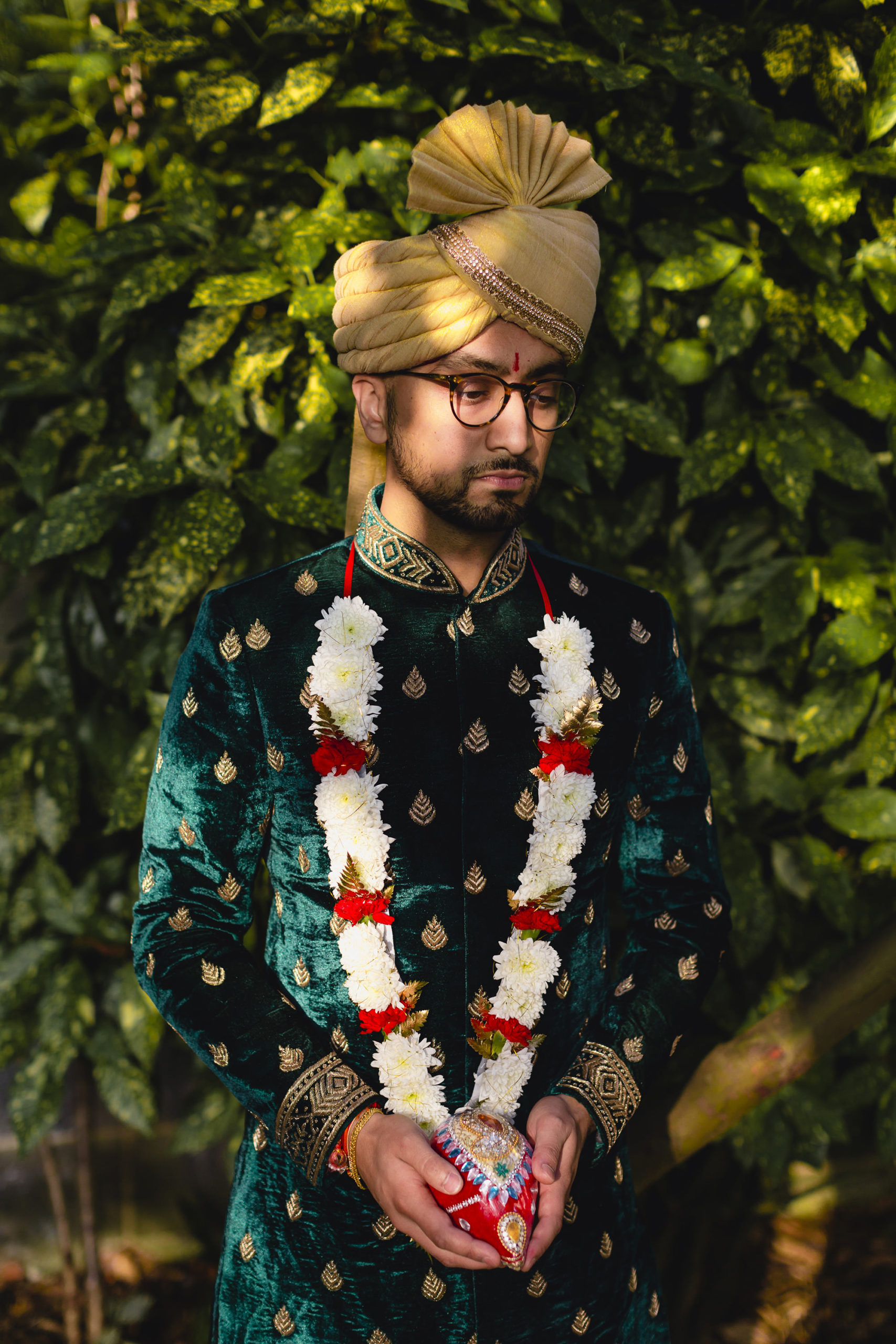 groom portrait in green wedding outfit