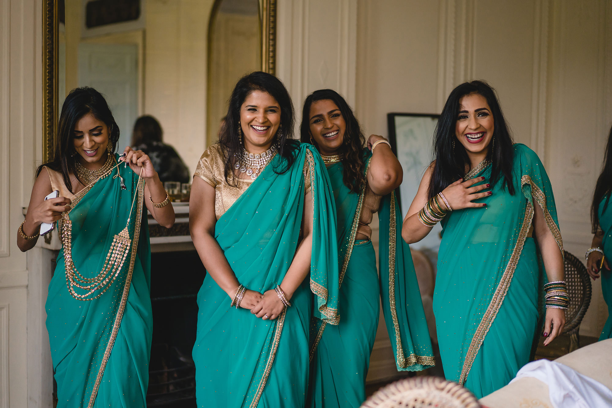 bridesmaids seeing the bride and showing excitement in green bridesmaids outfits