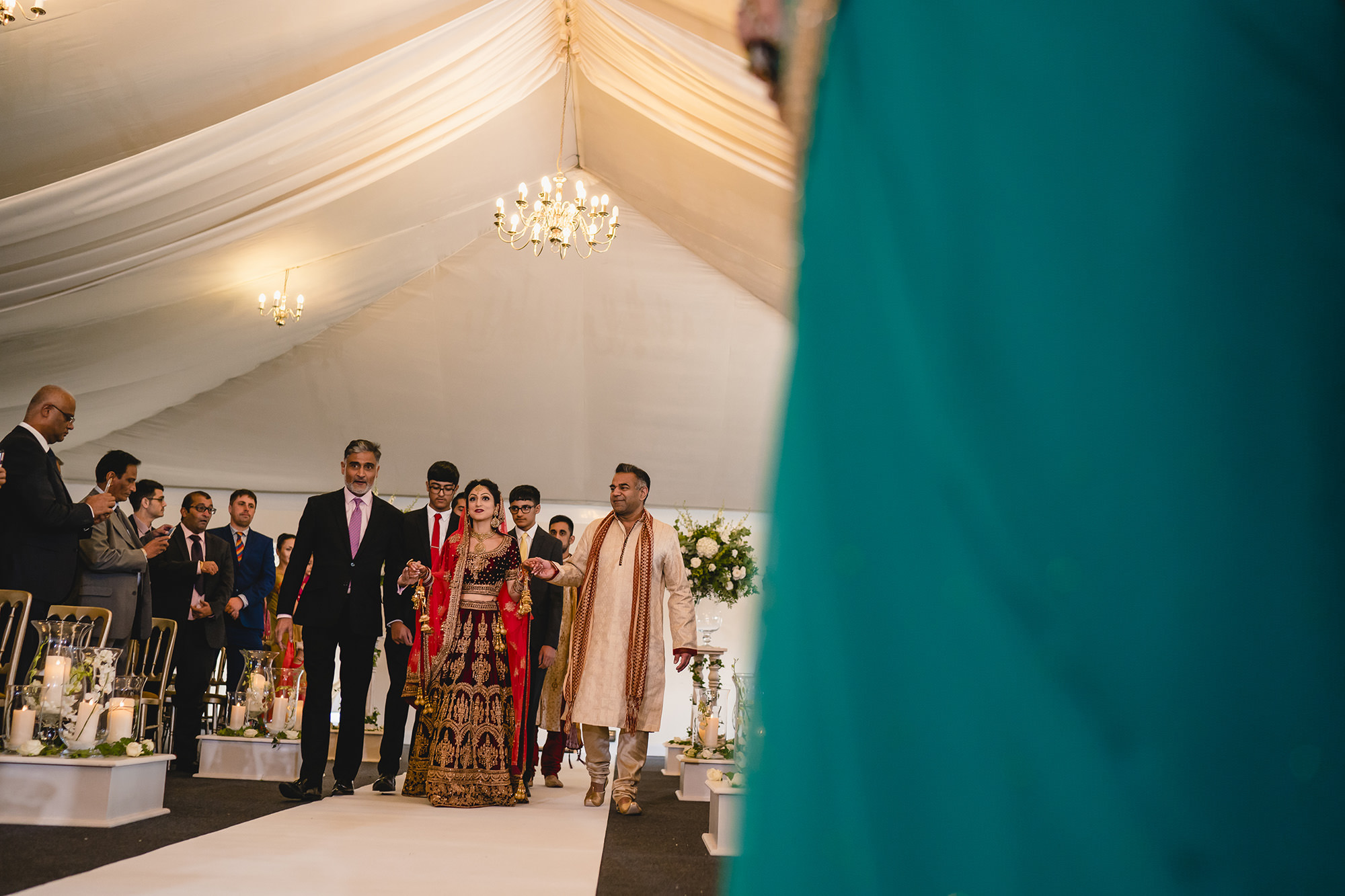 hindu bride entering the mandap accompanied by her uncles
