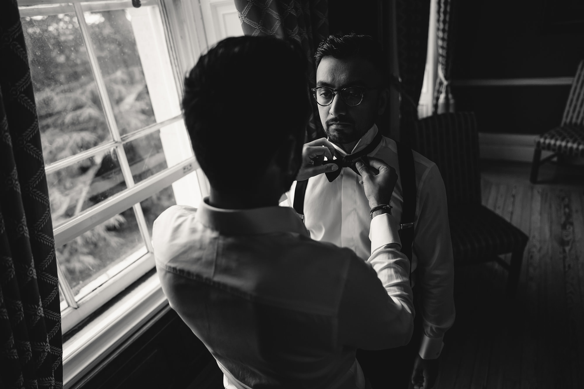 best man helping groom with wedding outfit