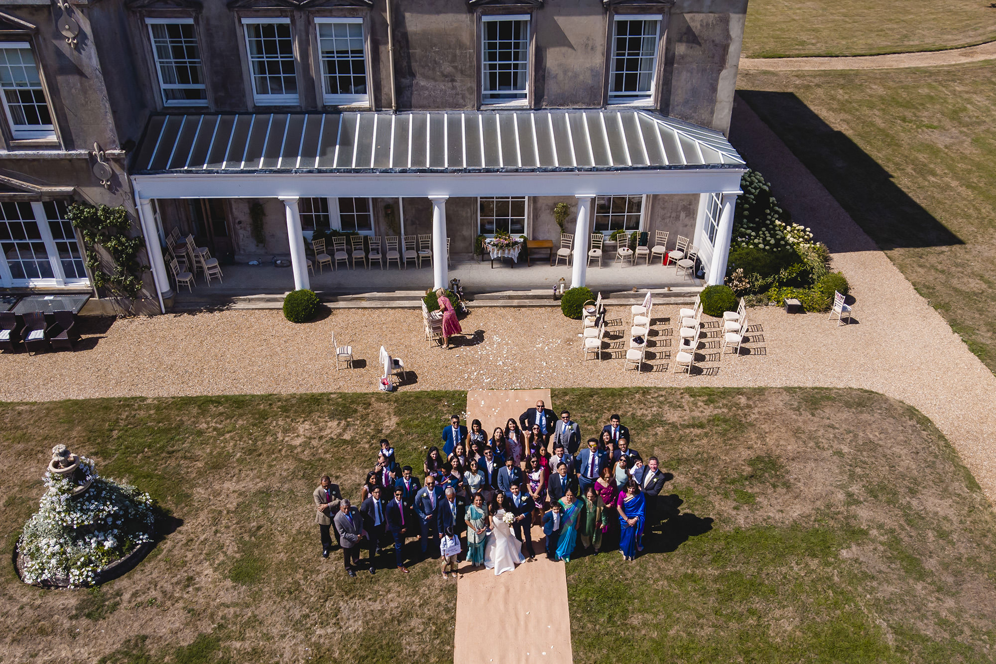 drone shot of all the guests at the civil ceremony with the venue behind them