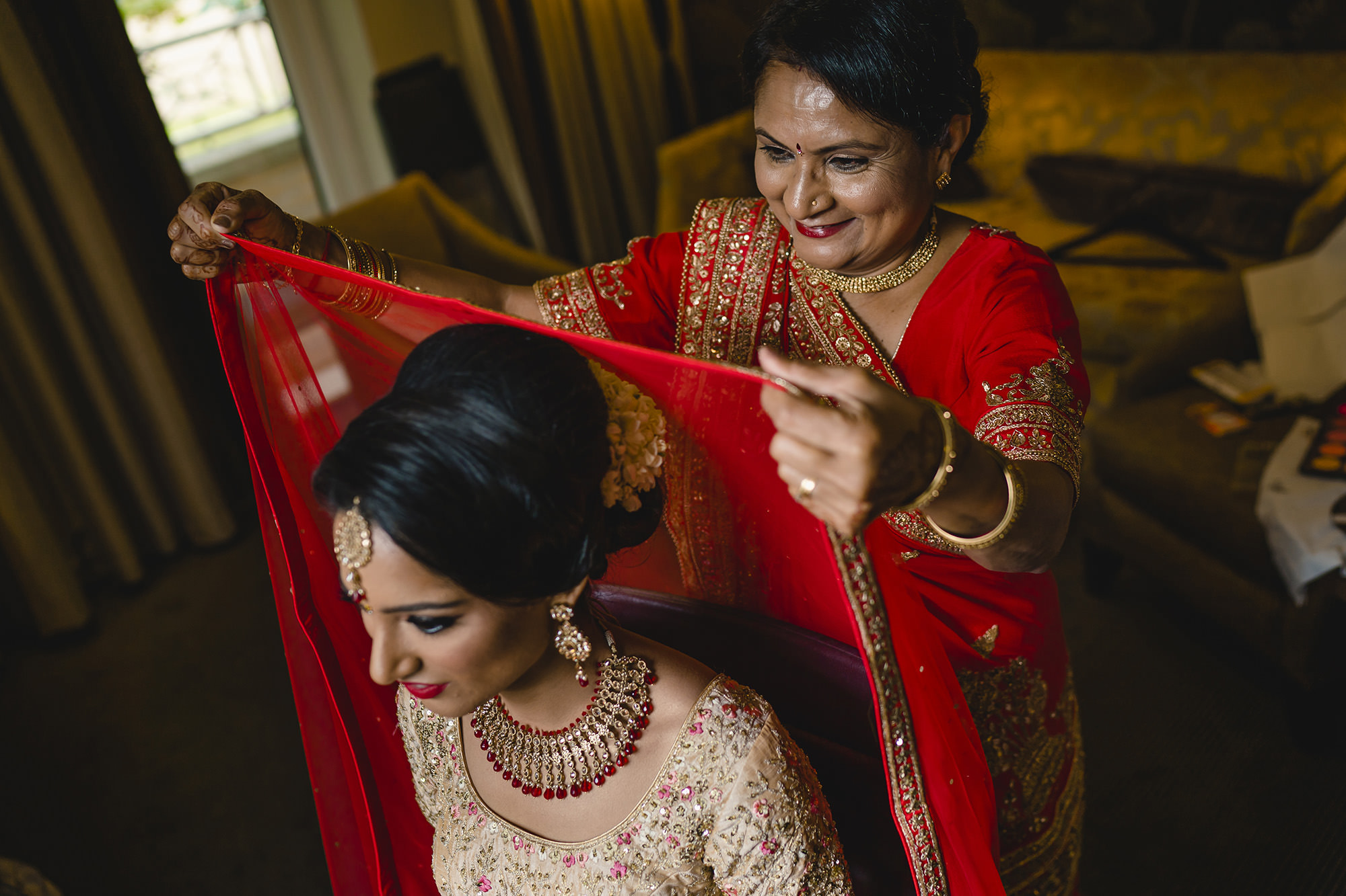 mum placing the dupatta on the brides forehead