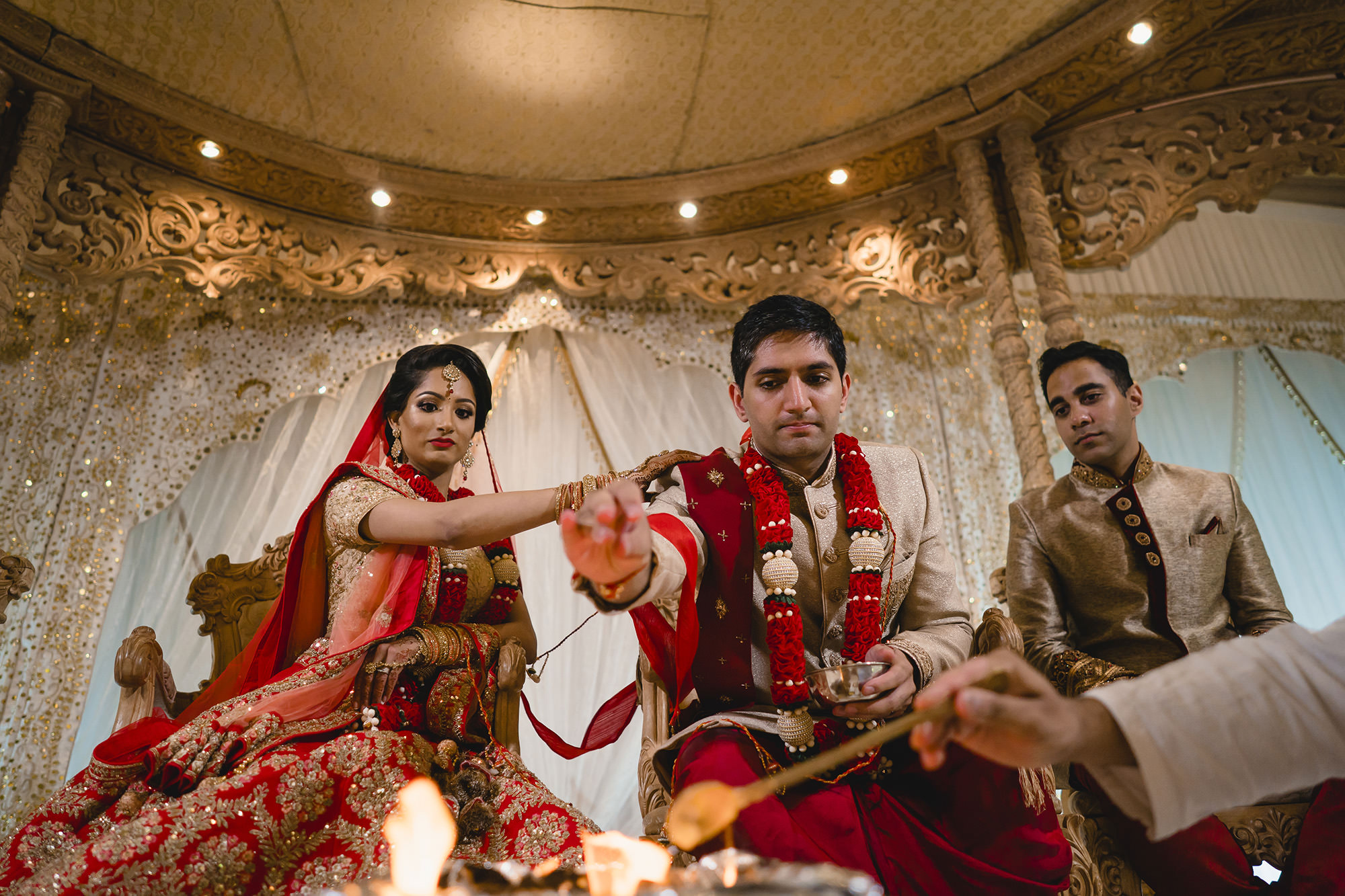 bride and groom feeding the fire as part of the hindu ceremony