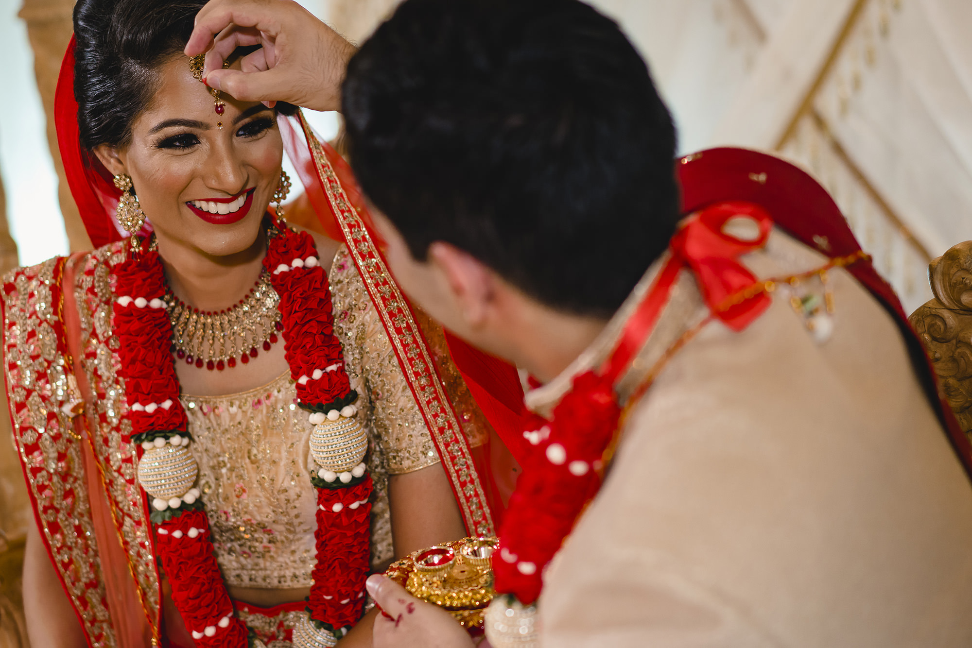 groom placing sindhoor on brides forehead to signify marriage