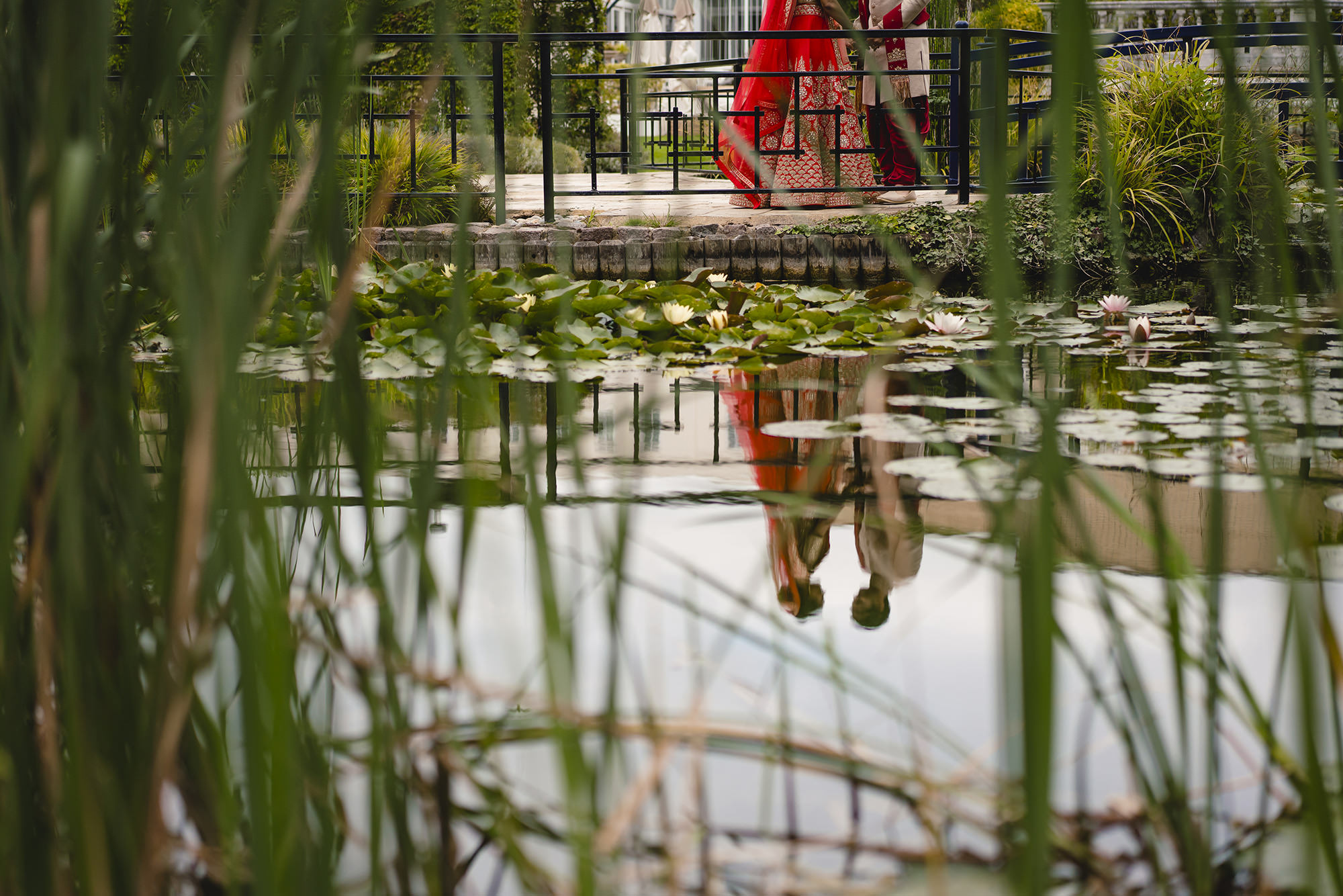 bride and groom reflected in the lake at sopwell house