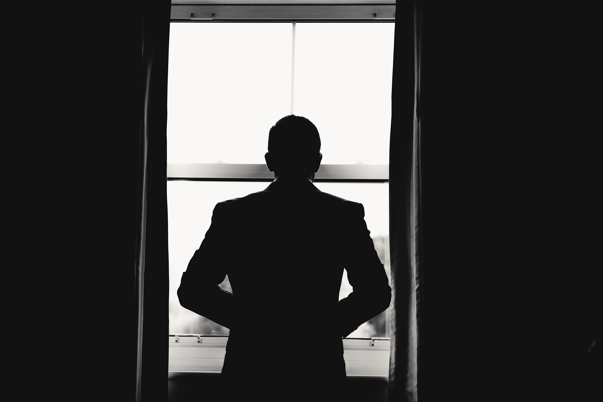 groom looking out the window in his reception outfit