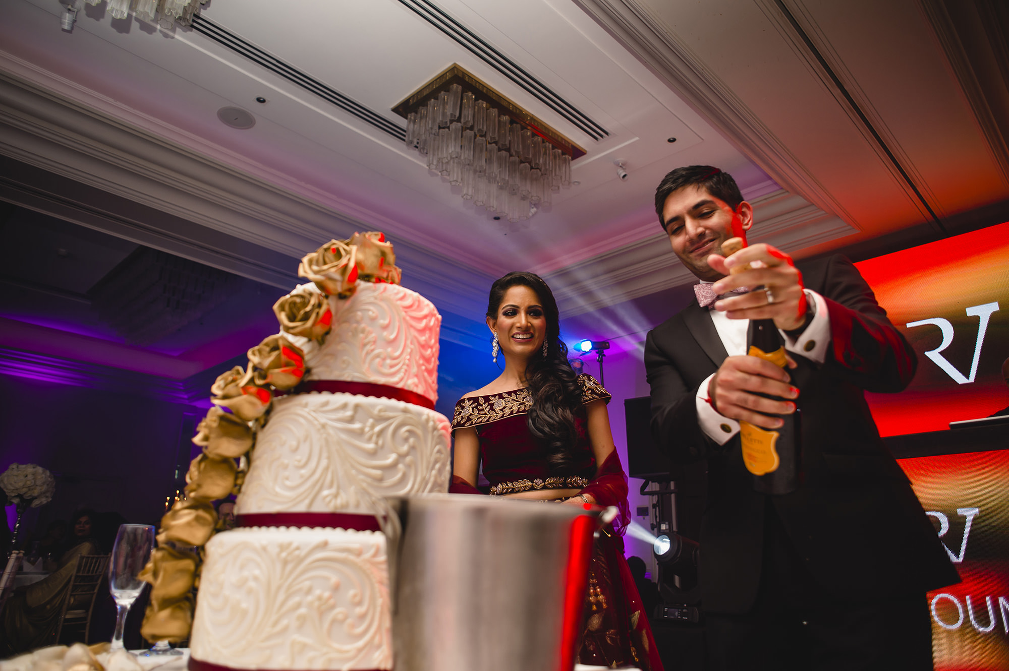 groom popping champagne after cutting wedding cake with bride