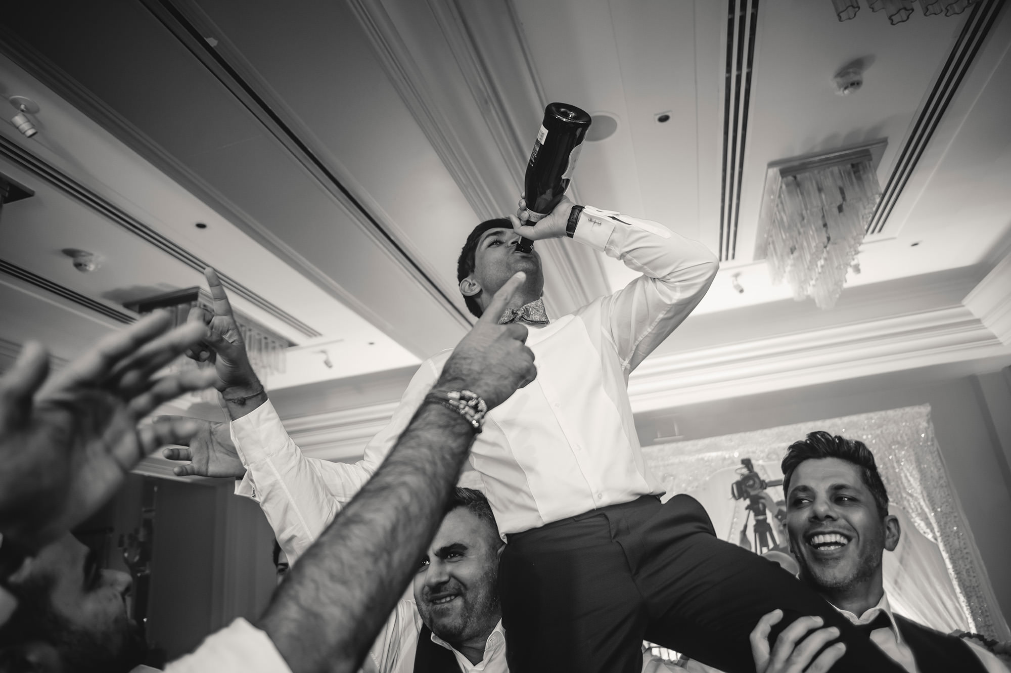 groom lifted by friends during wedding reception