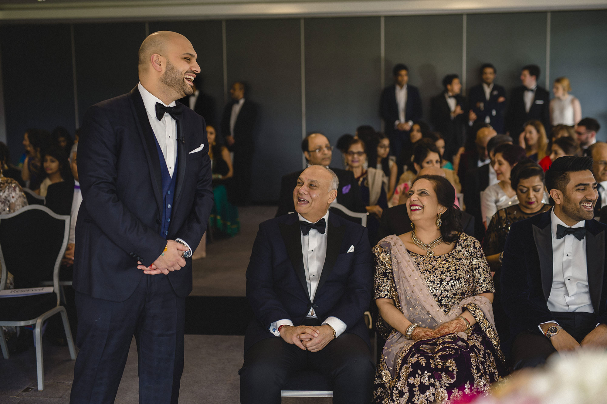 groom laughing with parents during civil ceremony