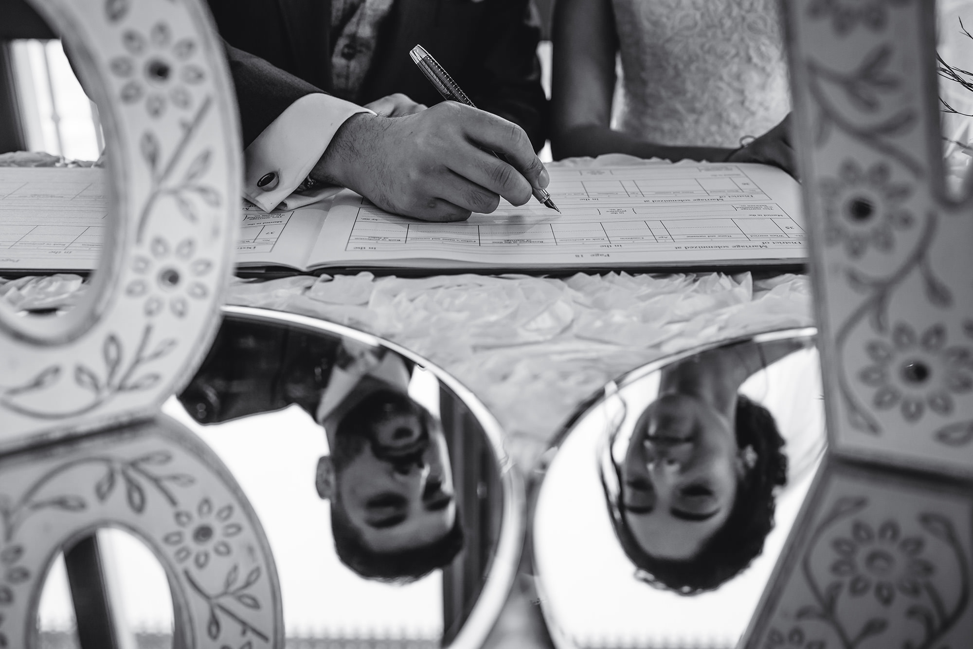 creative picture of the bride and groom signing the register at their civil wedding