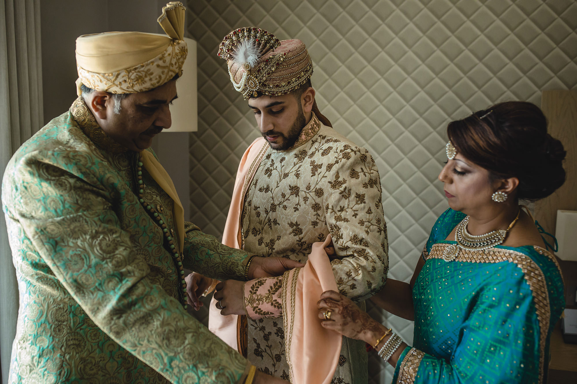 groom in his sherwani with his parents prior to the hindu wedding