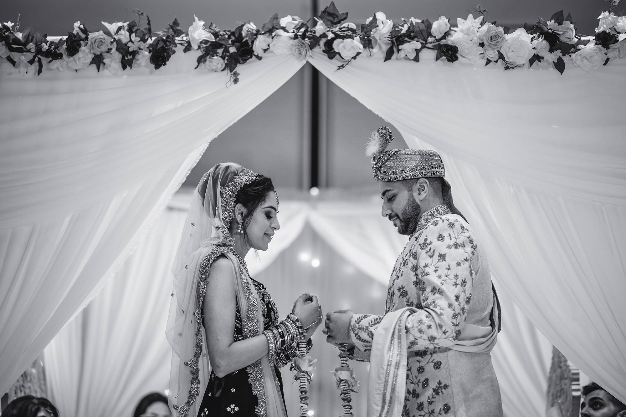 bride and groom exchanging garlands in the mandap
