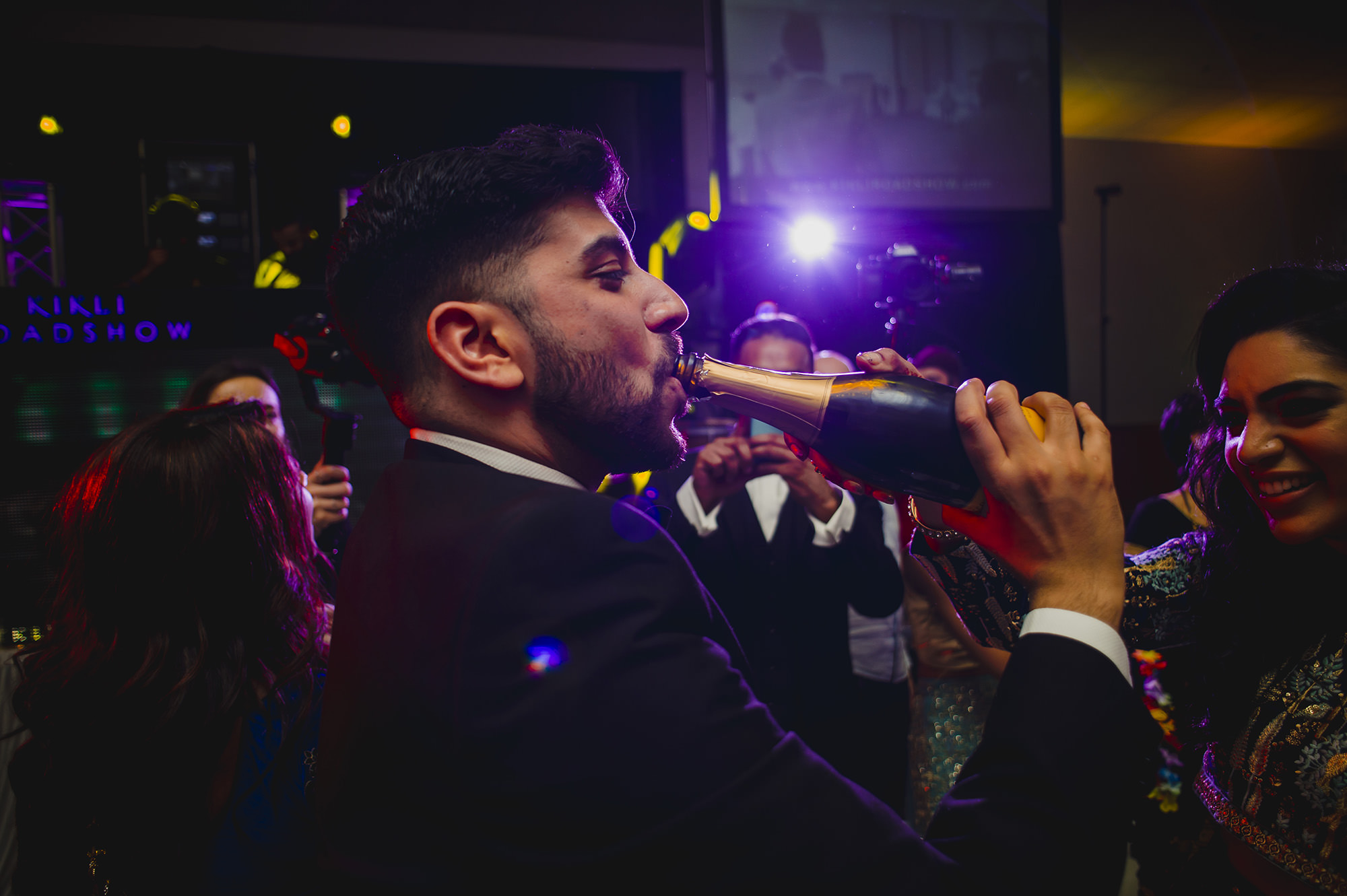 groom drinking from champagne bottle at his wedding reception