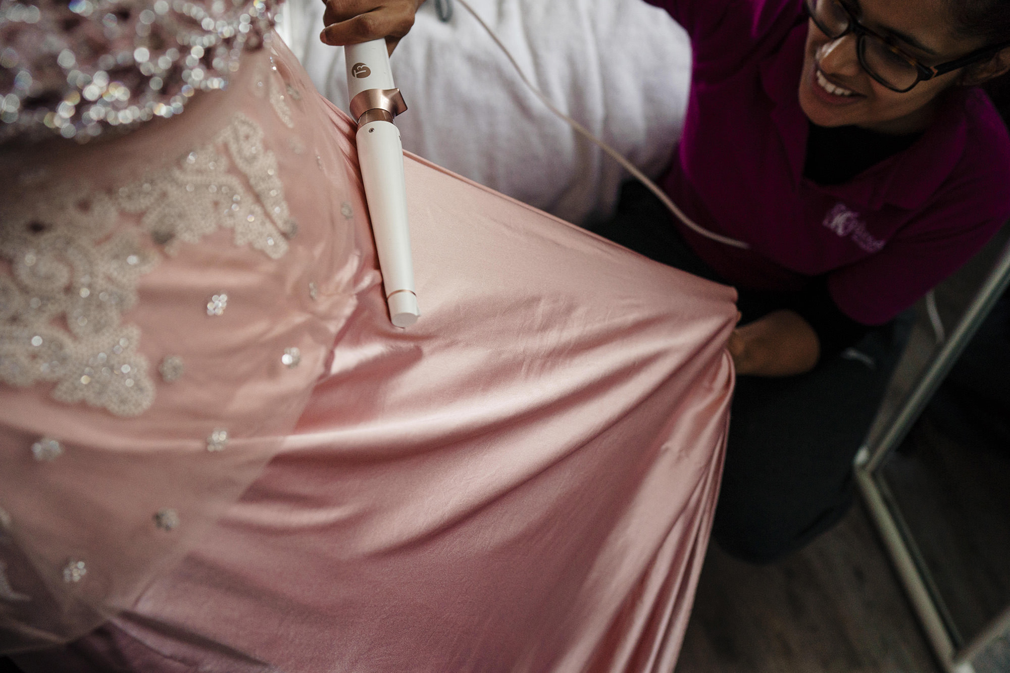 mua helping remove creases out of brides wedding dress