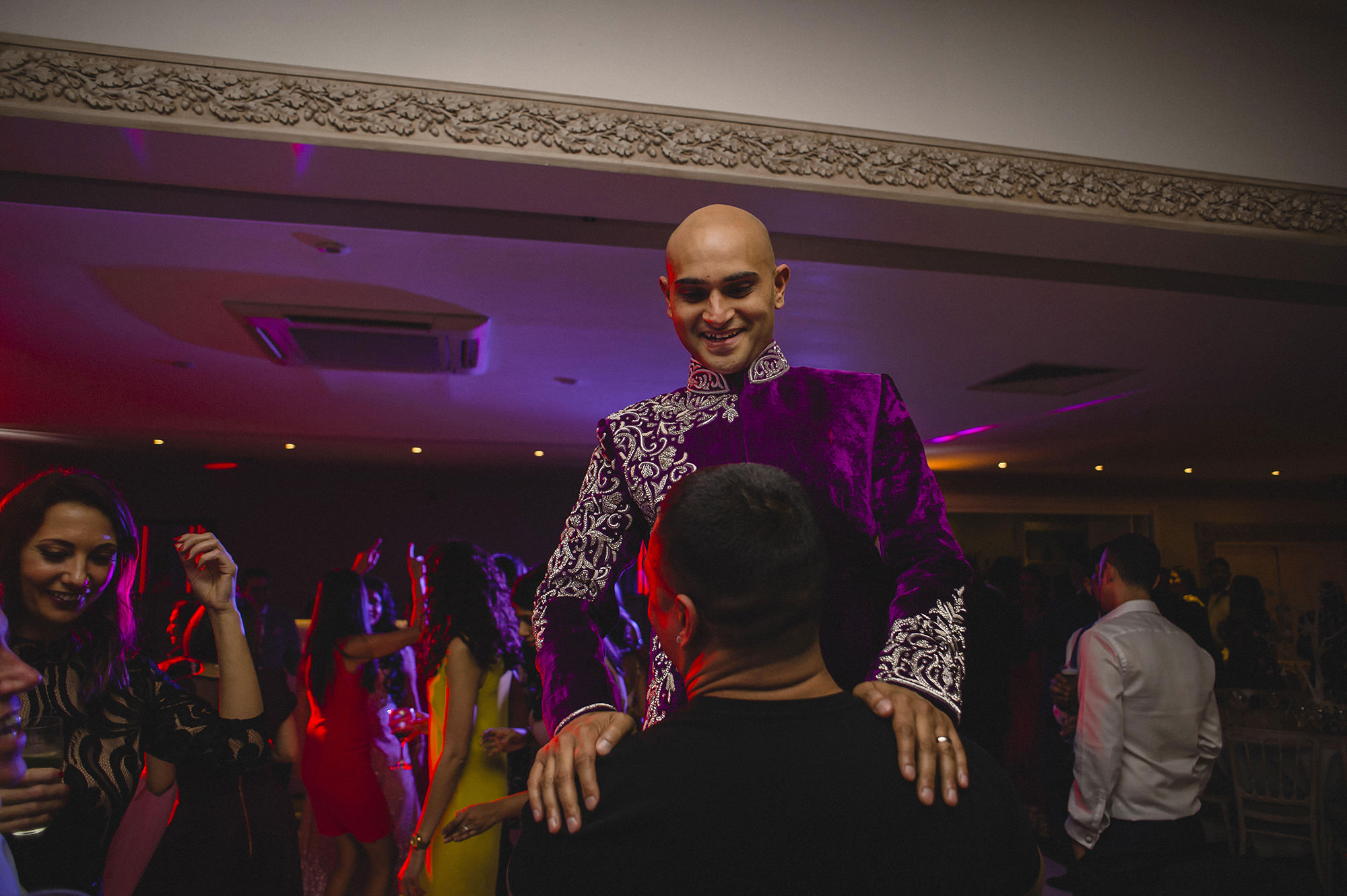 groom lifted by wedding guest at reception party