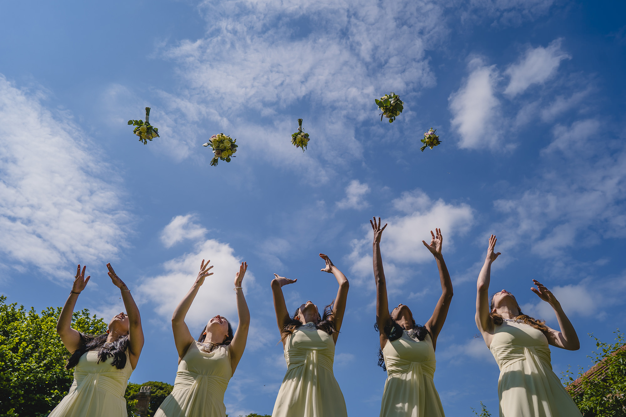 bridesmaids throwing their flowers in the air at poundon house