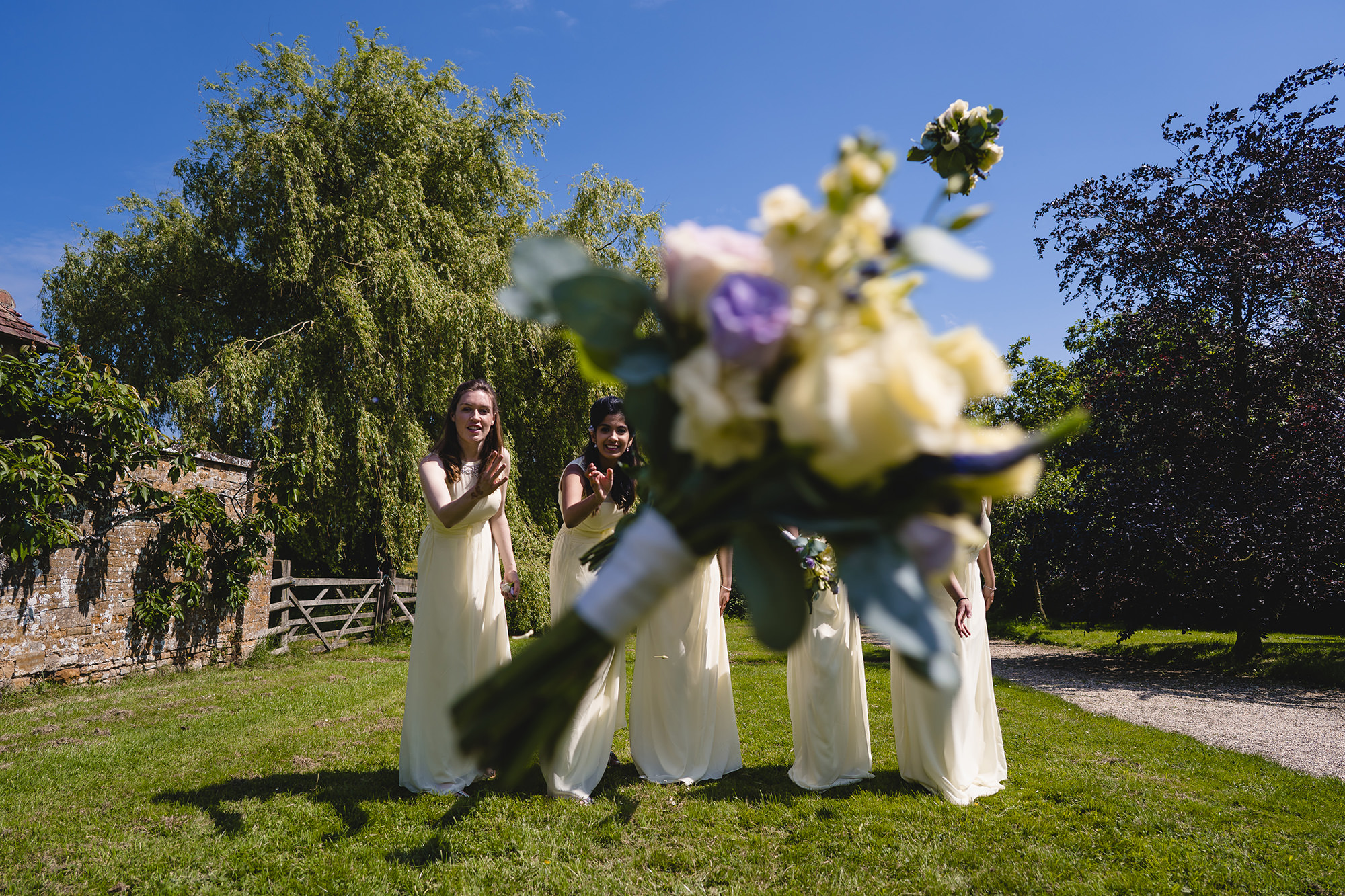 bridesmaids throwing their bouquet at the camera