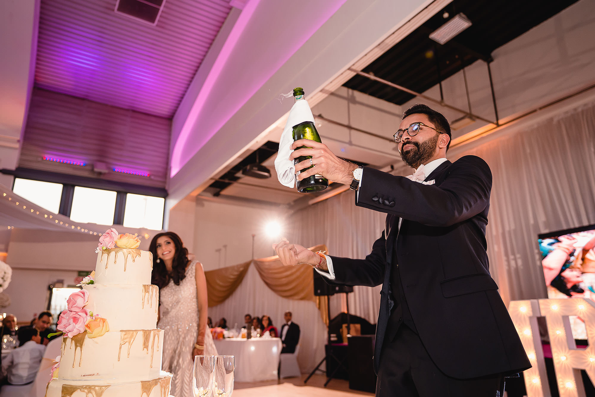 groom opening champagne bottle