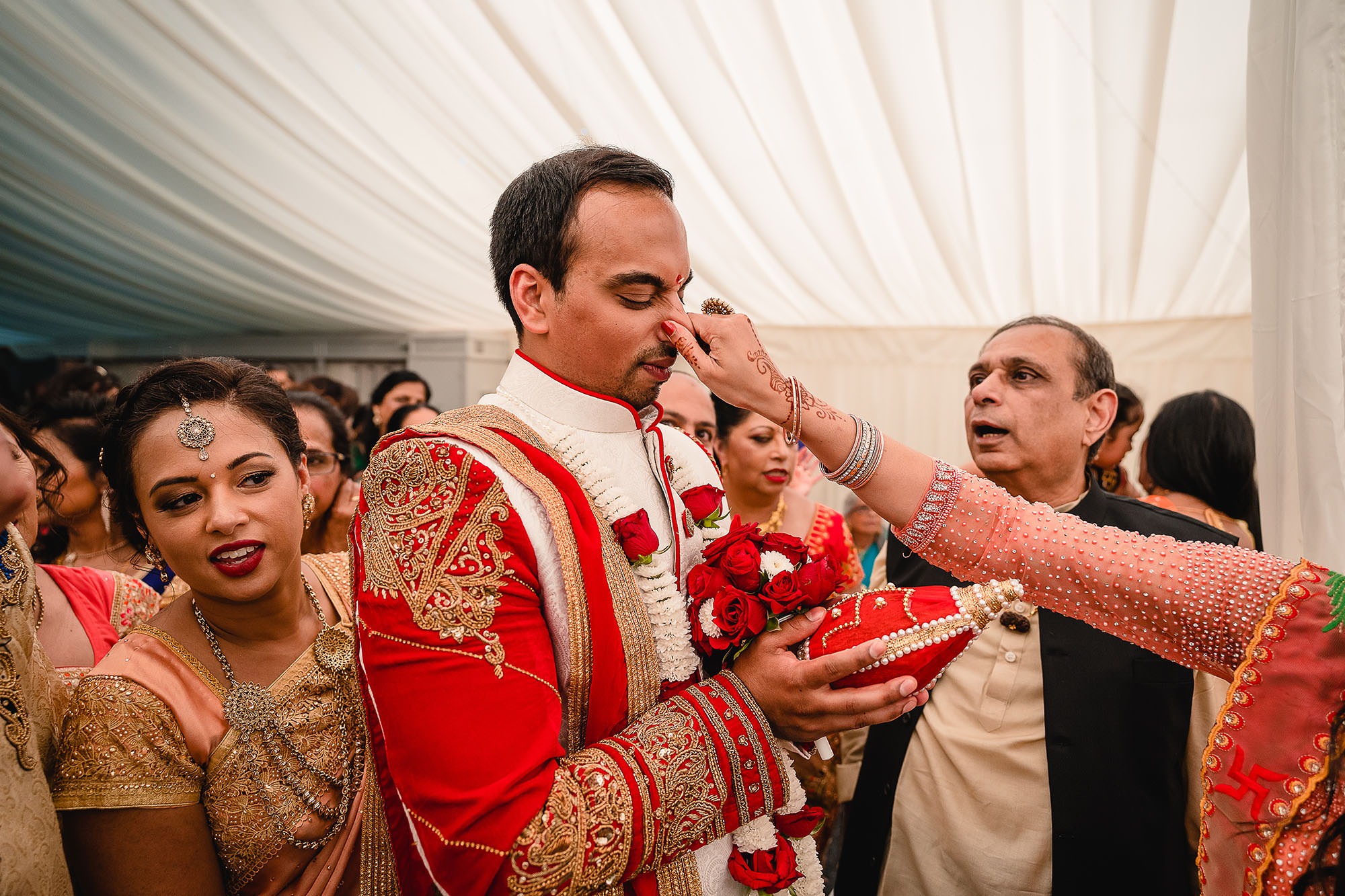 groom having his nose pinched at hindu wedding