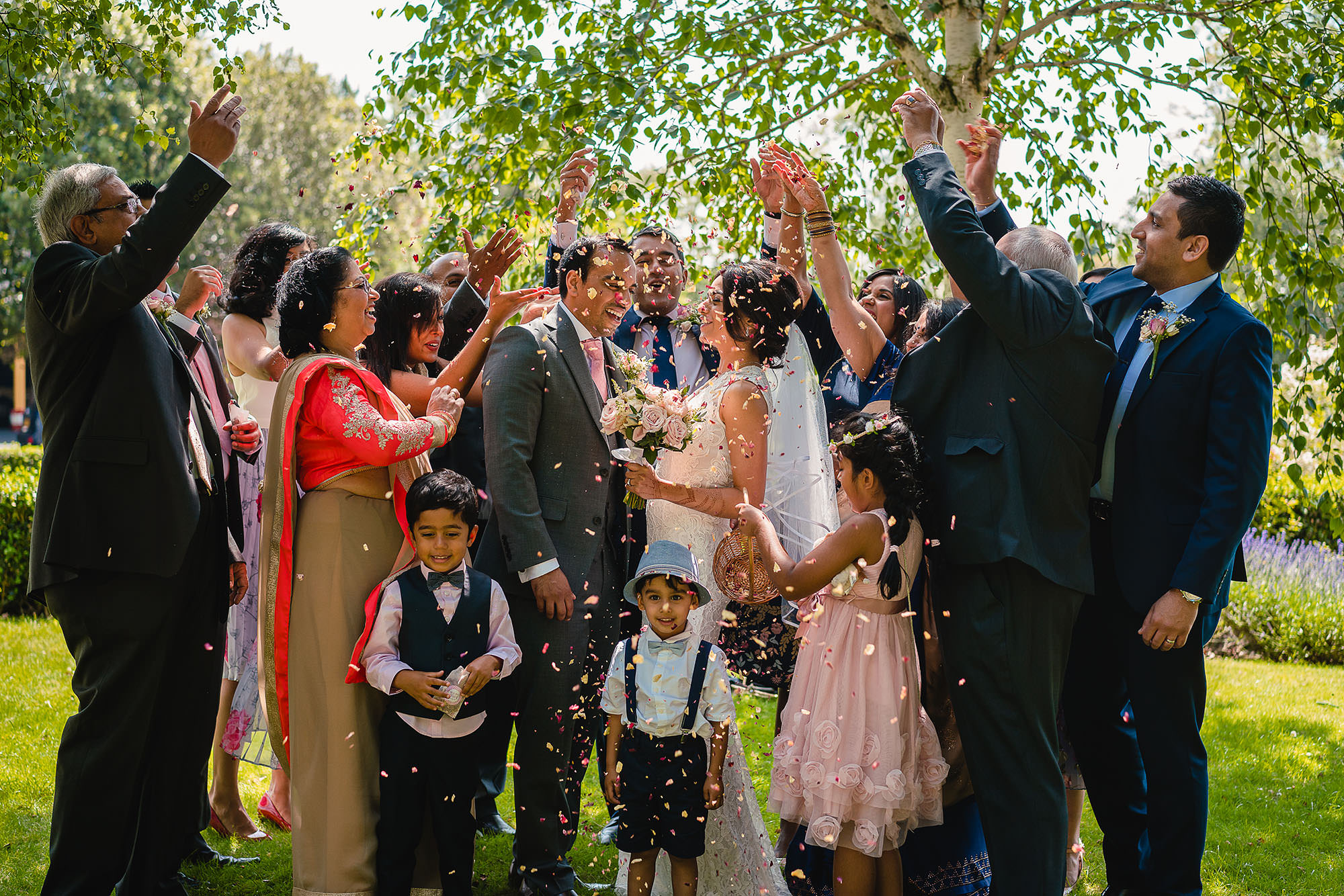 family showering the bride and groom with confetti