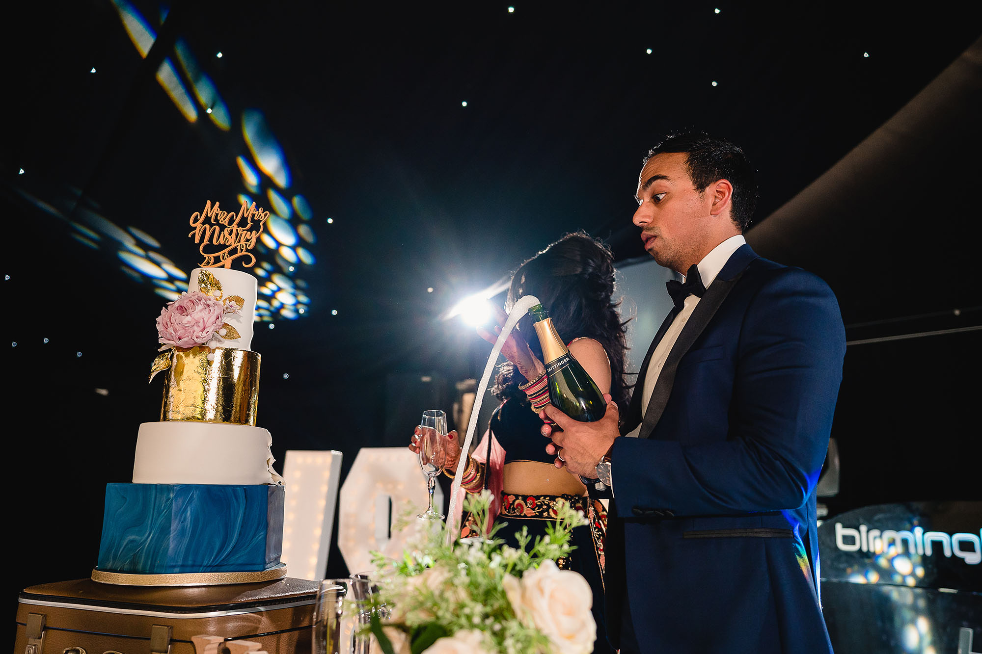 groom popping champagne cork