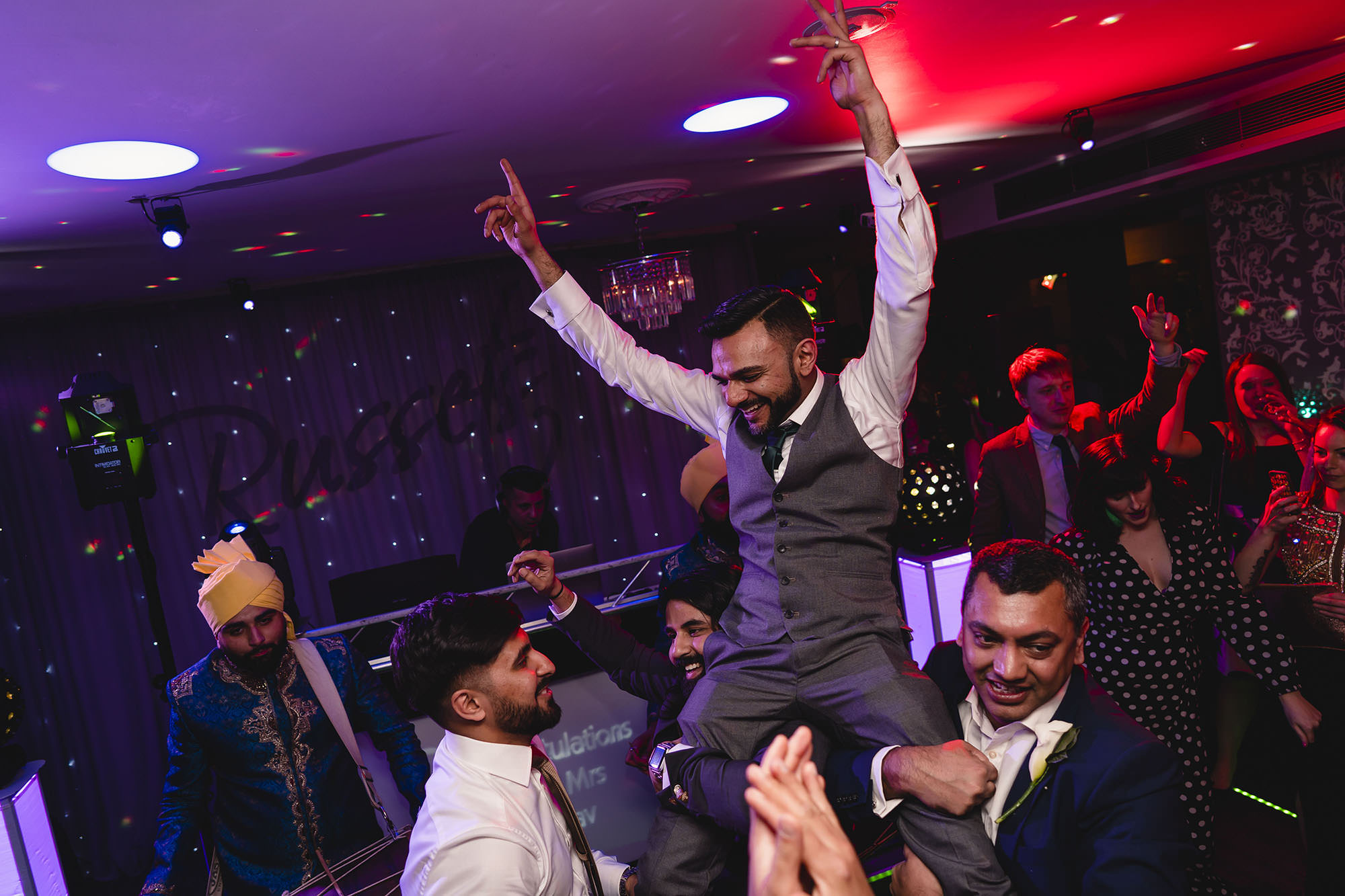 groom lifted onto shoulders during reception party