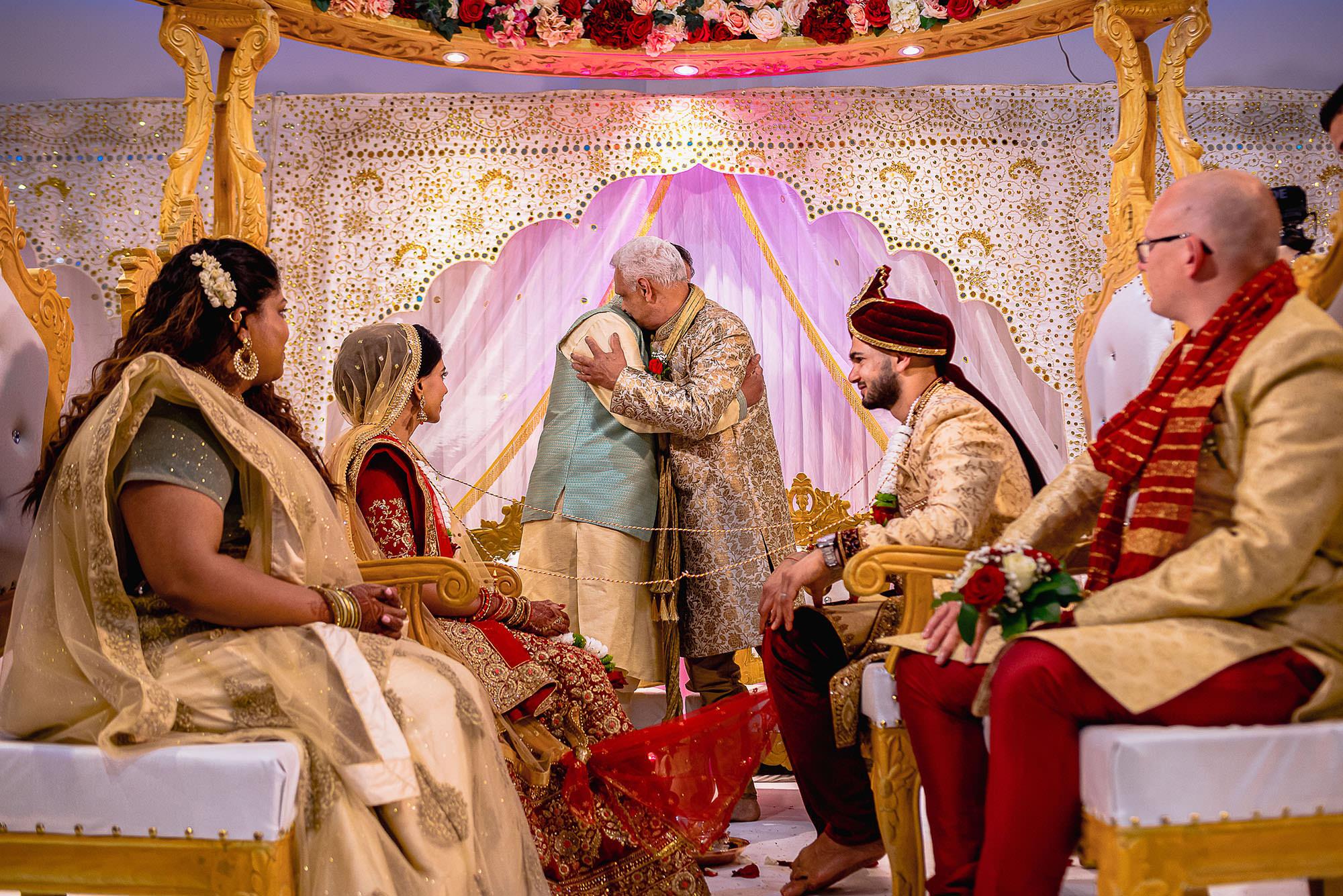 bride and groom parents hugging devan jigna